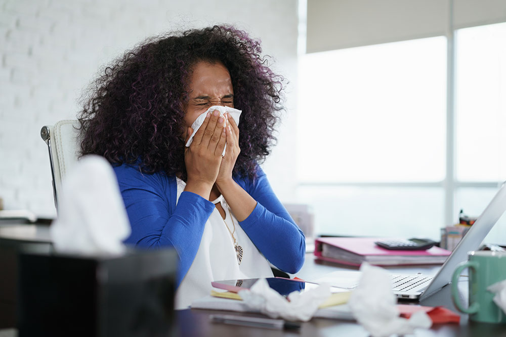 woman sneezing at desk, rights to paid time off during coronavirus