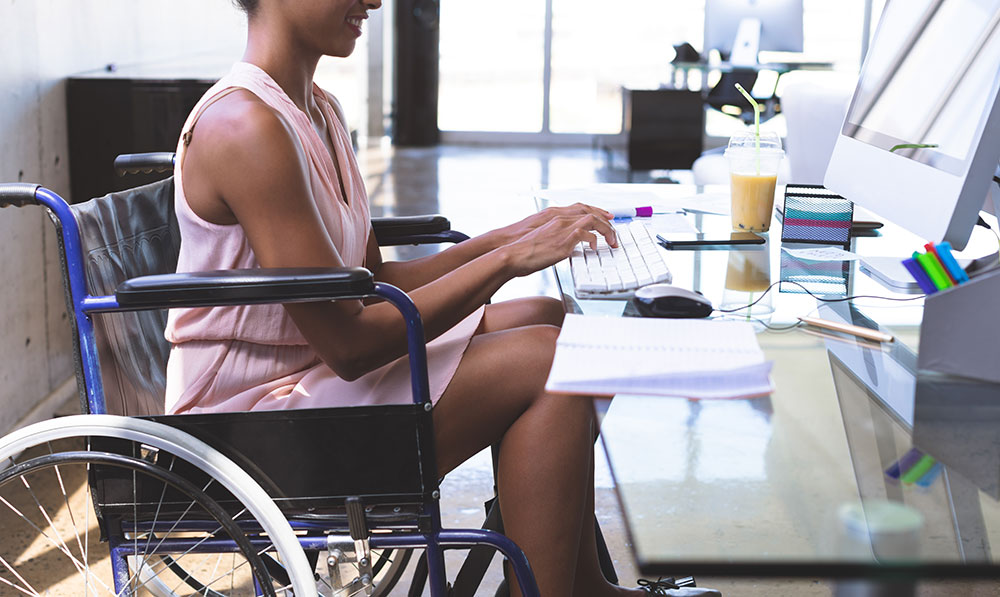 woman at desk in wheelchair, disability discrimination