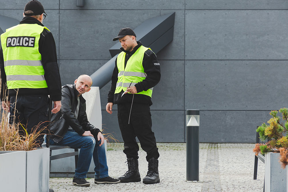 man sitting outside and being questioned by the police